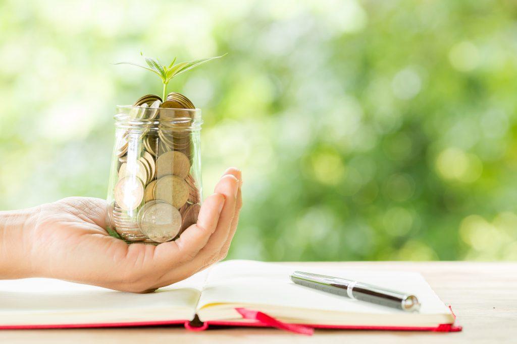 Chica sujetando un vaso de monedas encima de un libro por el día de la educación financiera